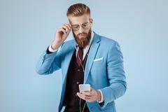Hombre elegante en auriculares con smartphone Foto de archivo