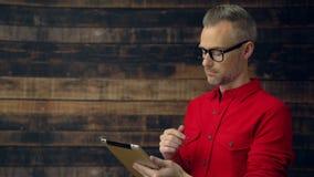 Hombre elegante en camisa roja usando la tableta excéntrica almacen de metraje de vídeo
