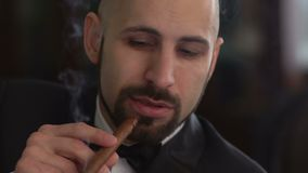 Hombre elegante en un traje que fuma un cigarro, cámara lenta almacen de video