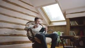 Hombre elegante en vidrios que lee un libro y que bebe el vino en el ático almacen de video