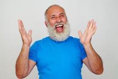 Hombre elegante envejecido que ríe sinceramente con las manos levantadas imagenes de archivo