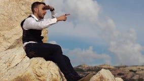 Hombre elegante hermoso en el pa?o de lujo que se sienta en las rocas y waching una visi?n asombrosa mientras que muestra algo a  almacen de metraje de vídeo