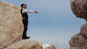 Hombre elegante hermoso en la situación de lujo del paño en las rocas y waching una visión asombrosa mientras que muestra algo a  metrajes