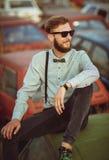 Hombre elegante hermoso joven, camisa que lleva y corbata de lazo con los coches viejos Fotos de archivo