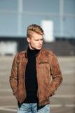Hombre elegante hermoso joven en chaqueta marrón en el tiempo del otoño al aire libre en estilo sport Fotos de archivo libres de regalías