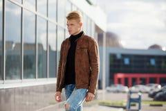 Hombre elegante hermoso joven en chaqueta marrón en el tiempo del otoño al aire libre en estilo sport Imagenes de archivo