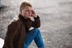 Hombre elegante hermoso joven en chaqueta marrón en el tiempo del otoño al aire libre en estilo sport Imagen de archivo