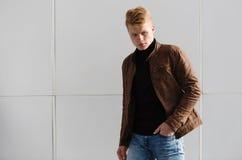 Hombre elegante hermoso joven en chaqueta marrón en el tiempo del otoño al aire libre en estilo sport Fotos de archivo