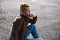 Hombre elegante hermoso joven en chaqueta marrón en el tiempo del otoño al aire libre en estilo sport Foto de archivo