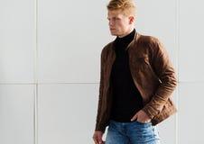 Hombre elegante hermoso joven en chaqueta marrón en el tiempo del otoño al aire libre en estilo sport Fotografía de archivo