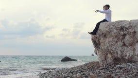 Hombre elegante hermoso que se sienta en las rocas y waching una visi?n asombrosa mientras que muestra algo a la gente con su fin metrajes