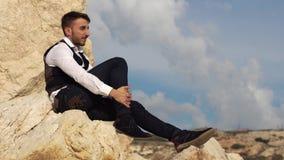 Hombre elegante hermoso sentarse en las rocas y waching una visión asombrosa chipre Paphos almacen de metraje de vídeo