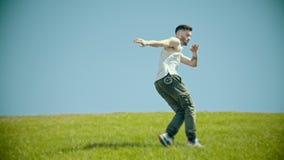 Hombre elegante joven con los tatuajes en el baile blanco de la camisa en la hierba fresca almacen de metraje de vídeo