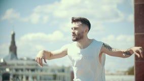 Hombre elegante joven con los tatuajes en el baile blanco de la camisa en el soporte en un fondo de la ciudad metrajes