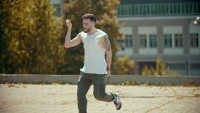 Hombre elegante joven con los tatuajes que bailan en la calle y que señalan en la gente almacen de video