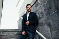Hombre elegante joven del hombre de negocios con una barba en un traje de moda y vaqueros Imagen moderna de la juventud del negoc imágenes de archivo libres de regalías