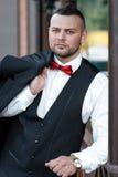 Hombre elegante joven en un traje Retrato del novio El novio está sosteniendo chaqueta en su hombro Imagen de archivo libre de regalías