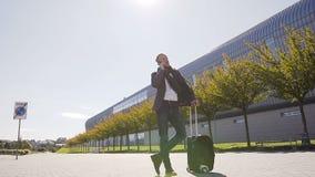 Hombre elegante joven que habla en su situación del teléfono con la maleta mientras que sale el aeropuerto outdoors Estilo del as metrajes