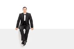 Hombre elegante joven que se sienta en un panel en blanco Imágenes de archivo libres de regalías