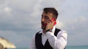 Hombre elegante lindo joven que habla por la c?lula cerca de vista lateral de mar que sorprende Hombre de negocios que habla por  metrajes