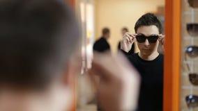 Hombre elegante que busca las mejores gafas de sol almacen de video