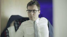 Hombre elegante que pone en una chaqueta y las gafas de sol almacen de video