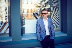 Hombre elegante elegante que se coloca en la calle foto de archivo