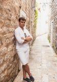 Hombre elegante que se inclina contra la pared de piedra vieja en la calle Imágenes de archivo libres de regalías
