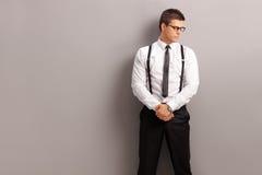 Hombre elegante que se opone a una pared gris Imagen de archivo libre de regalías