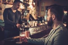 Hombre elegante que se sienta solamente en el contador de la barra con una pinta de cerveza foto de archivo