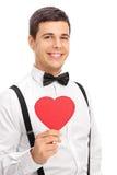 Hombre elegante que sostiene una cartulina en forma de corazón Foto de archivo libre de regalías