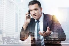 Hombre elegante que tiene negociaciones del negocio en el teléfono Fotos de archivo libres de regalías
