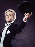 Hombre elegante vestido que lanza el sombrero negro del sombrero de ala Fotografía de archivo