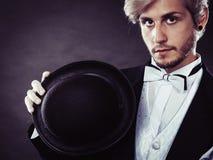 Hombre elegante vestido que sostiene el sombrero negro del sombrero de ala Foto de archivo