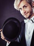 Hombre elegante vestido que sostiene el sombrero negro del sombrero de ala Imagen de archivo libre de regalías
