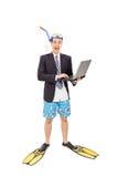 Hombre emocionado con la máscara del salto que trabaja en el ordenador portátil Foto de archivo libre de regalías