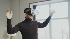 Hombre emocionado con las auriculares de la realidad virtual que juegan al videojuego 360 en casa fotografía de archivo