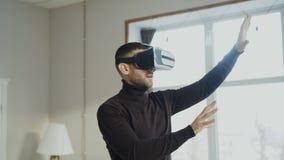 Hombre emocionado con las auriculares de la realidad virtual que juegan al videojuego 360 en casa imagen de archivo