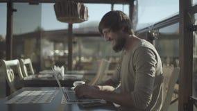 Hombre emocionado de la barba que celebra éxito mientras que trabaja en el ordenador portátil Sin graduar CRUDO almacen de video
