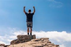 Hombre emocionado en el top en un paisaje hermoso del verano foto de archivo