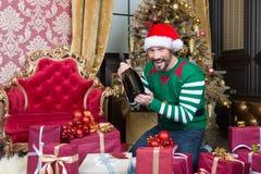 Hombre emocionado en traje del duende que sonríe y que sostiene la botella grande fotografía de archivo libre de regalías