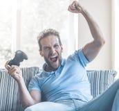 Hombre emocionado fascinado por el juego en la consola en casa fotos de archivo libres de regalías