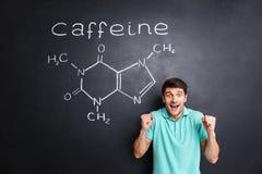 Hombre emocionado feliz que celebra éxito sobre la estructura exhausta de la molécula del cafeína Fotografía de archivo libre de regalías