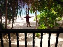 Hombre emocionado feliz que coloca el centro turístico isleño tropical del chalet frente al mar delantero Imagen de archivo