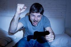 Hombre emocionado joven en casa que se sienta en el sofá de la sala de estar que juega a los videojuegos usando la palanca de man Foto de archivo