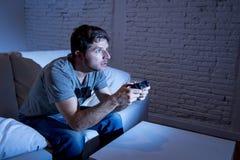 Hombre emocionado joven en casa que se sienta en el sofá de la sala de estar que juega a los videojuegos usando la palanca de man Imagen de archivo