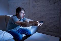 Hombre emocionado joven en casa que se sienta en el sofá de la sala de estar que juega a los videojuegos usando la palanca de man Fotografía de archivo