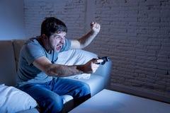 Hombre emocionado joven en casa que se sienta en el sofá de la sala de estar que juega a los videojuegos usando la palanca de man Fotografía de archivo libre de regalías