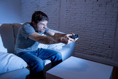 Hombre emocionado joven en casa que se sienta en el sofá de la sala de estar que juega a los videojuegos usando la palanca de man Imagen de archivo libre de regalías