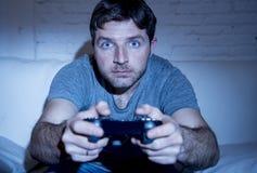 Hombre emocionado joven en casa que se sienta en el sofá de la sala de estar que juega a los videojuegos usando la palanca de man Fotos de archivo libres de regalías
